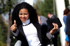 Smiling woman with a tablet showing thumb up. Outdoor. Ok sign. (focus on hand Stock Images