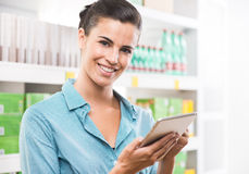 Smiling woman with tablet at supermarket Stock Photos