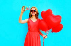 smiling woman takes a picture self portrait on smartphone hold stock images