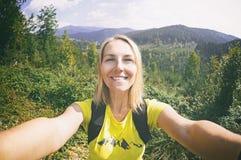 Smiling  woman takes a selfie  on mountain peak Royalty Free Stock Photo