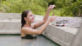 Smiling woman taking bath in thermal pool and applying mud mask on face skin. Beautiful woman in thermal water pool.  stock video