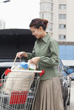 Smiling woman taking groceries out of shopping cart in front of her car Stock Photo
