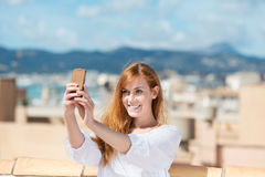 Smiling woman taking her photograph Royalty Free Stock Image