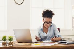 Smiling woman taking notes at office. Young smiling african-american businesswoman taking notes, sitting at modern office workplace. Timetable planning, time Royalty Free Stock Images