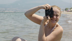 Smiling woman taking a photo at the seaside with her vintage camera stock video
