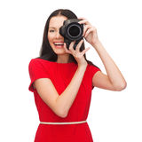 Smiling woman taking picture with digital camera Royalty Free Stock Images