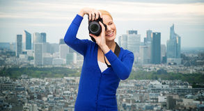 Smiling woman taking picture with digital camera Stock Photo