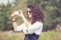 Smiling woman taking picture with a smart phone Royalty Free Stock Images