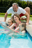 Smiling woman taking selfie with family in swimming pool. Woman taking selfie with family in swimming pool Royalty Free Stock Images