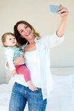 Smiling woman taking a selfie with her baby Royalty Free Stock Photos