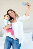 Smiling woman taking a selfie with her baby Royalty Free Stock Photography