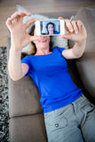 Smiling woman taking a selfie on her mobile phone. Smiling woman, on the couch, taking a selfie on her  mobile phone Royalty Free Stock Photo