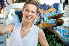 Smiling woman taking selfie near mosaic dragon in Park Guell Royalty Free Stock Image