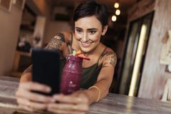 Woman taking a selfie for her food blog. Smiling woman taking a selfie with a smoothie placed in front of her using a mobile phone for her food blog. Food stock image
