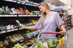 Smiling woman taking a vegetables in the aisle Royalty Free Stock Images