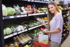Smiling woman taking a vegetables in the aisle Stock Photo