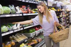 Smiling woman taking a vegetables in the aisle Stock Image