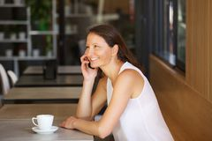 Smiling woman talking on cell phone at cafe Stock Photos