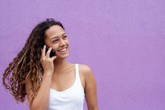Smiling woman talking on cell phone and looking away Stock Photo