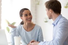Smiling woman talking with colleague during break at workplace. Smiling women talking with colleague during break at workplace, happy female worker share stock photography
