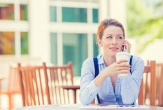 Smiling woman talking on mobile phone outside corporate office building Royalty Free Stock Photos