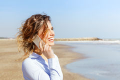 Smiling woman talking on the mobile phone at the seaside Royalty Free Stock Photos