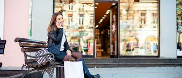 Smiling woman talking on mobile phone after shopping Stock Image