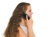 Smiling woman talking mobile phone. Side view Royalty Free Stock Images