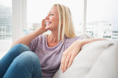 Smiling woman talking on mobile phone on sofa Royalty Free Stock Images