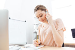 Smiling woman talking on mobile phone and writing in office Royalty Free Stock Photography
