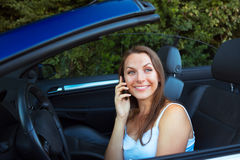 Smiling woman talking on phone in a cabriolet car Stock Image