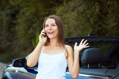 Smiling woman talking on phone in a cabriolet car Stock Images
