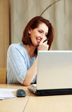 Smiling woman talking on the phone at her workplace Royalty Free Stock Photos