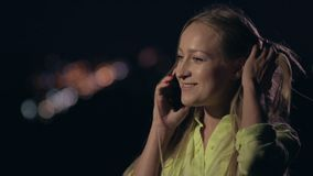Smiling woman talking on phone at night city stock video