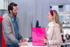 Smiling woman talking to cashier Stock Photo