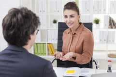 Smiling woman is talking to her colleague Royalty Free Stock Images