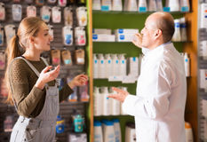 Smiling woman talking to a pharmacist royalty free stock image
