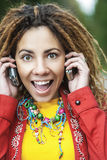 Smiling woman talking on two mobile phone Stock Photos