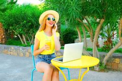 smiling woman talks on a smartphone, laptop computer on a cafe Royalty Free Stock Photo