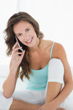 Smiling woman in tank top using mobile phone in bed Stock Photos