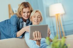Smiling woman teaching her grandmother how to use a modern device stock image