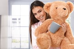 Smiling woman with teddy bear and coffee mug Royalty Free Stock Photography