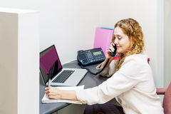Smiling woman on telephone at office desk Royalty Free Stock Photo