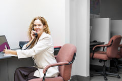 Smiling woman on telephone at office desk. Businesswoman on phone taking notes in office workstation Royalty Free Stock Photography