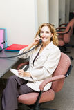 Smiling woman on telephone at office desk. Businesswoman on phone taking notes in office workstation Stock Photo