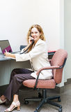 Smiling woman on telephone at office desk. Businesswoman on phone talking and taking notes in office workstation Stock Photo