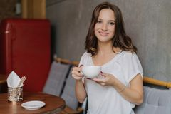 Smiling woman with tender smile, holds cup of tea or coffee, enjoys good rest, poses in cozy cafe or restaurant, waits for friend, royalty free stock images