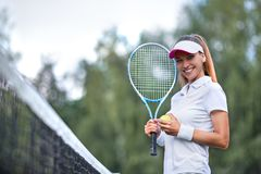 Smiling woman with a tennis racket royalty free stock photo