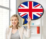 Smiling woman with text bubble of british flag. Education, fogeign language, english, people and communication concept - smiling woman holding text bubble of royalty free stock image