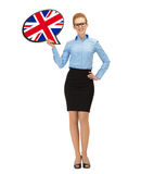 Smiling woman with text bubble of british flag. Education, foreign language, english, people and communication concept - smiling woman holding text bubble of royalty free stock photo